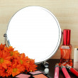 Round table mirror with cosmetics and flowers on table on wooden background — Stock Photo #34819471