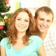 Happy young couple near Christmas tree at home — Stock Photo #34820085