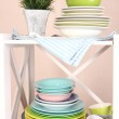 Beautiful white shelves with tableware and decor, on color wall background, close-up — Stock Photo #34823671