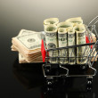 Shopping trolley with dollars, on dark background — Stock Photo #34826779