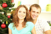 Happy young couple near Christmas tree at home — Stock Photo