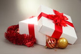 Gift box with bright light on it on grey background — Stock Photo