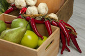 Fruits and vegetables in crates on wooden background — Stock Photo