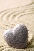 Gray zen stone in shape of heart, on sand background — Stock Photo