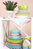 Beautiful white shelves with tableware and decor, on color wall background, close-up — Stock Photo
