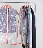 Office female clothes in cases for storing on hangers, on gray background — Stock Photo