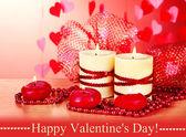 Hermosas velas con una decoración romántica en una mesa de madera sobre un fondo rojo — Foto de Stock