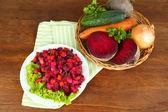 Beet salad on plate on napkin on wooden table — Stock Photo