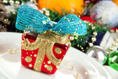 Small Christmas gift on plate on serving Christmas table background close-up — Stockfoto
