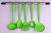 Plastic kitchen utensils on silver hooks on lilac background — Stock Photo
