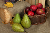 Ripe fruits in basket on sackcloth background — Stock Photo