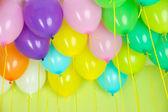 Kolorowe balony na tle zielony ściana — Zdjęcie stockowe