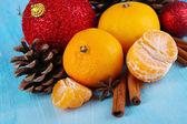 Composición de navidad con mandarinas en mesa de madera sobre fondo azul — Foto de Stock