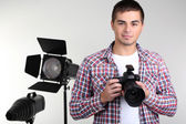 Handsome photographer with camera, on photo studio background — Stock Photo