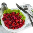 Beet salad on plate on napkin on wooden board isolated on white — Stock Photo #34859163