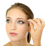 Young woman plucking eyebrows isolated on white — Stock Photo