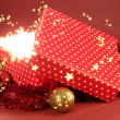 Gift box with bright light on it on red background — Stockfoto