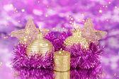 Composición de navidad con velas y decoraciones en colores púrpuras y oro sobre fondo brillante — Foto de Stock
