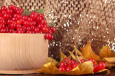 Red berries of viburnum in wooden bowl with yellow leaves on table on brown background — Photo