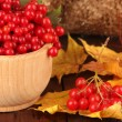 Red berries of viburnum in wooden bowl with yellow leaves on table on brown background — Stock Photo #34993325