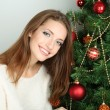 Beautiful smiling girl sitting near Christmas tree in room — Stock Photo #34994375