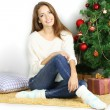 Beautiful smiling girl sitting near Christmas tree in room — Stock Photo #34994745