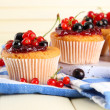 Tasty muffins with berries on white wooden table — Stock Photo #34995775