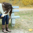 Young lonely woman on bench in park — Stock Photo #34995997