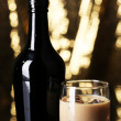 Baileys liqueur in bottle and glass on golden background — Stock Photo #34996949
