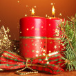 Two candles and christmas decorations, on brown background — Stock Photo #34998829