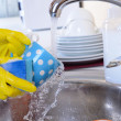 Close up hands of woman washing dishes in kitchen — Stock Photo #34998987
