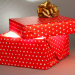 Gift box with bright light on it on grey background — Stock Photo #34999147