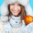 Beautiful smiling girl with Christmas ball on blue background — Stock Photo #34999157