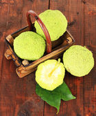 Osage Orange fruits (Maclura pomifera) in basket, on wooden background — Stock Photo
