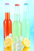 Drinks in glass bottles with ice cubes on blue background — Stock Photo
