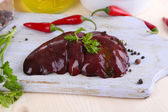 Raw liver on wooden board with spices and condiments on wooden table close-up — Stock Photo