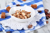 Many toffee in bowl on napkin on wooden table — Stock Photo