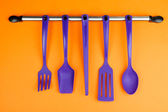 Plastic kitchen utensils on silver hooks on orange background — Stock Photo