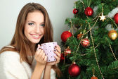 Beautiful smiling girl sitting near Christmas tree — Foto de Stock