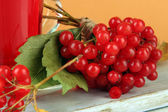 Red berries of viburnum and cup of tea on table on beige background — 图库照片