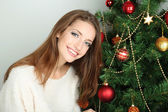 Beautiful smiling girl sitting near Christmas tree in room — Foto de Stock