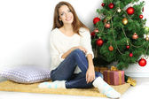 Krásná usměvavá dívka sedí u vánočního stromu v místnosti — Stock fotografie