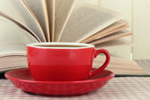 Cup of coffee and book on tablecloth on wooden background — 图库照片