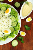 Delicious salad with eggs, cabbage and cucumbers on wooden table — Stock Photo