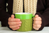 Cup in female hands — Stock Photo