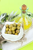 Olives in bowl with branch on sackcloth on wooden board on table — Stock Photo