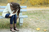 Young lonely woman on bench in park — Foto Stock