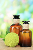 Osage Orange fruits (Maclura pomifera) and medicine bottles, on wooden table, on nature background — Stock Photo
