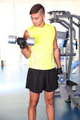 Guy with dumbbells in gym — Stock Photo
