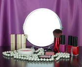 Round table mirror with cosmetics and chaplet on table on fabric background — Stock Photo